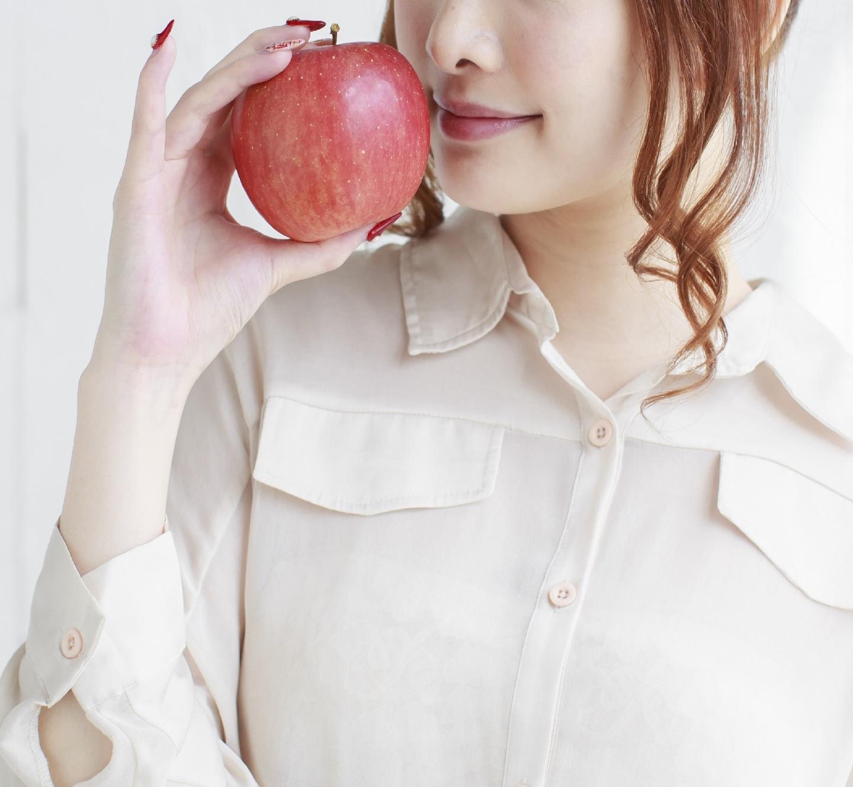 リンゴを持って微笑む女性